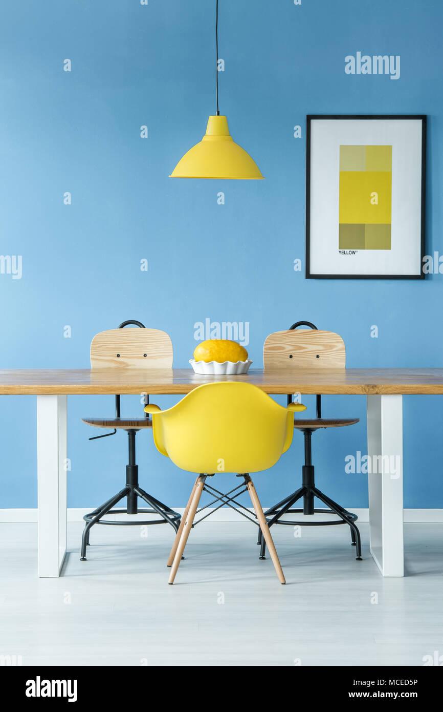 Estilo minimalista interior simétrica con una lámpara amarilla colgando sobre una mesa de madera con un melón en un plato, sillas y un cartel sobre una pared azul Imagen De Stock