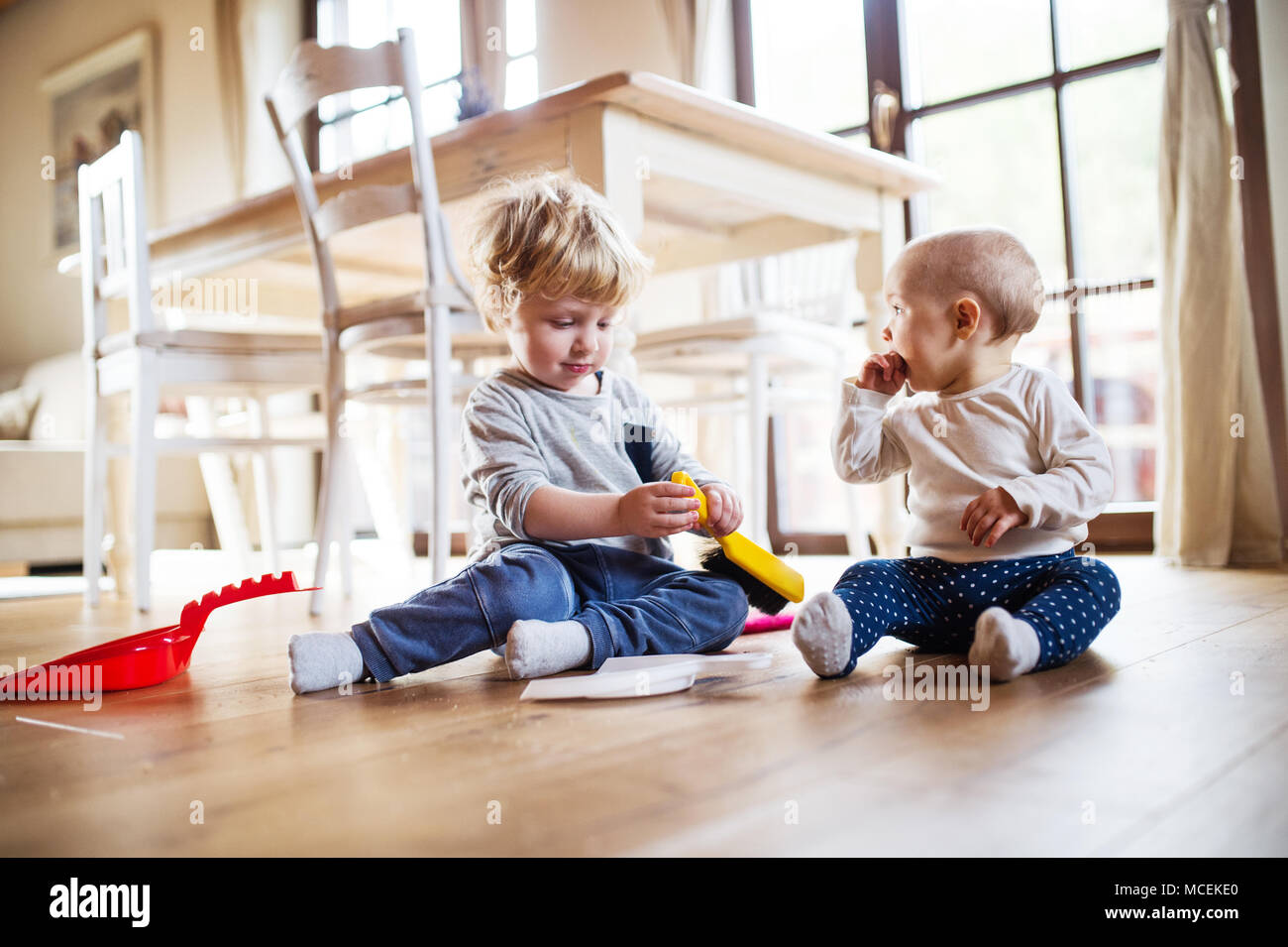 Dos niños con cepillo y pala para recoger basura en casa. Imagen De Stock