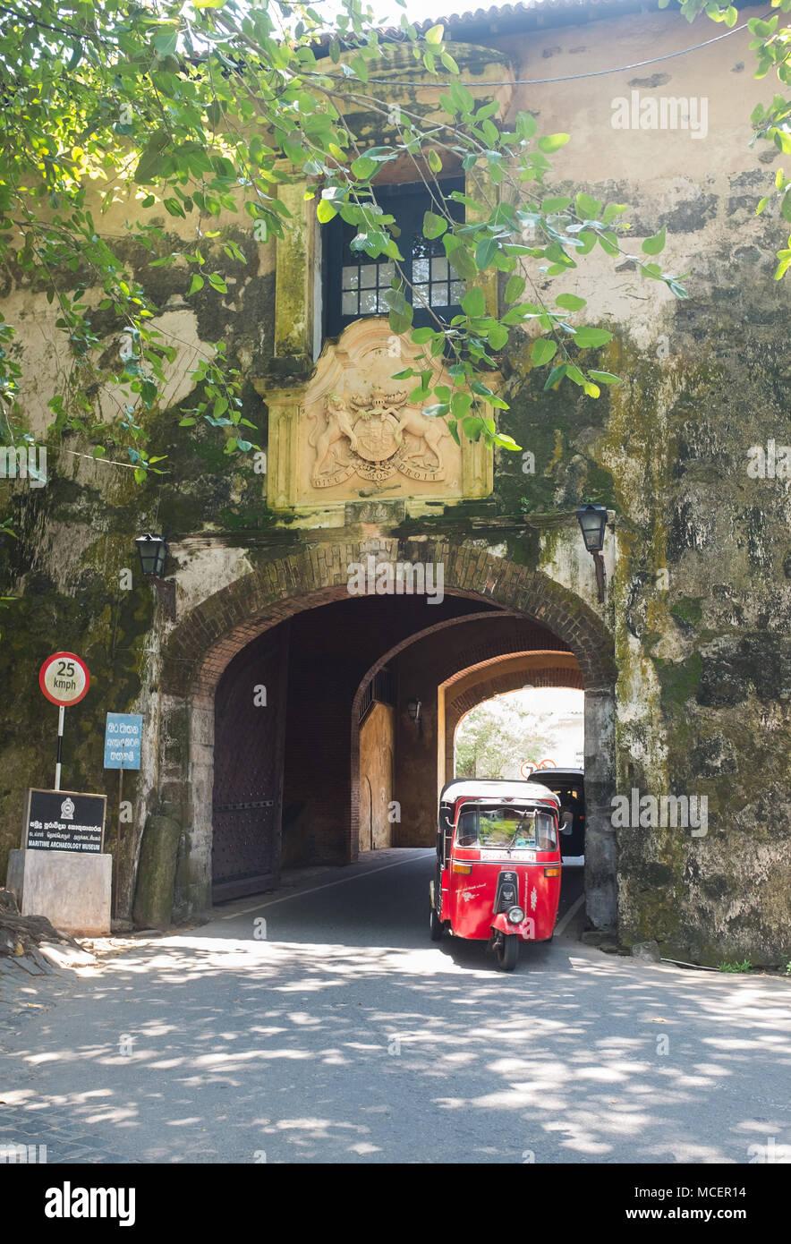 Tuk tuk pasaba por debajo de la antigua puerta de Galle, Sri Lanka, Asia. Imagen De Stock