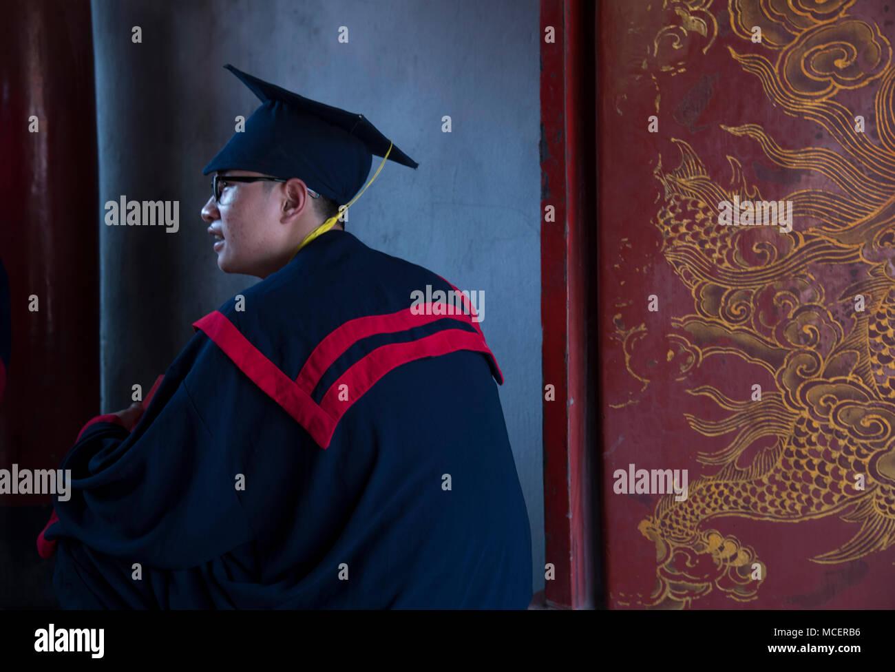 26f1362e3 Un niño vestido con una túnica con rayas rojas para la ceremonia de su  graduación en