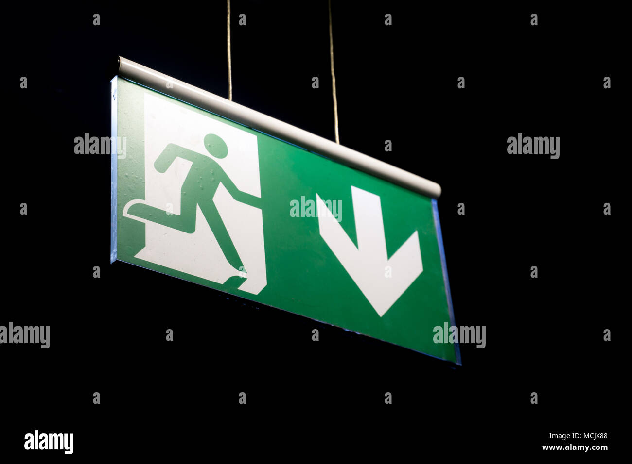Salida de emergencia cartel colgado en una pared. Señal de salida de emergencia en un edificio iluminado en color verde Foto de stock
