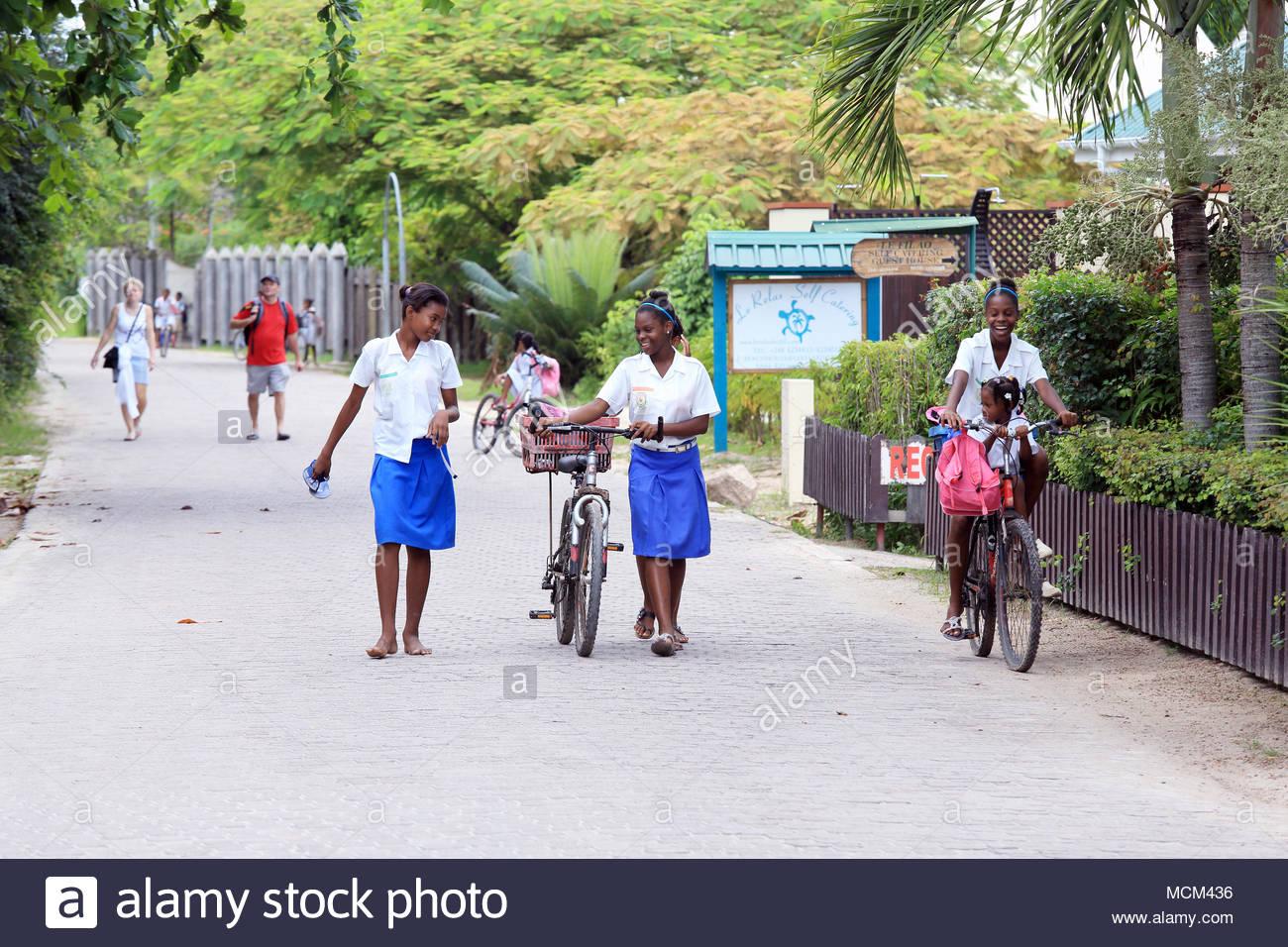 La Passe, La Digue Island, Seychelles - Marzo 5, 2014: Los estudiantes que abandonan la escuela en bicicletas. Imagen De Stock