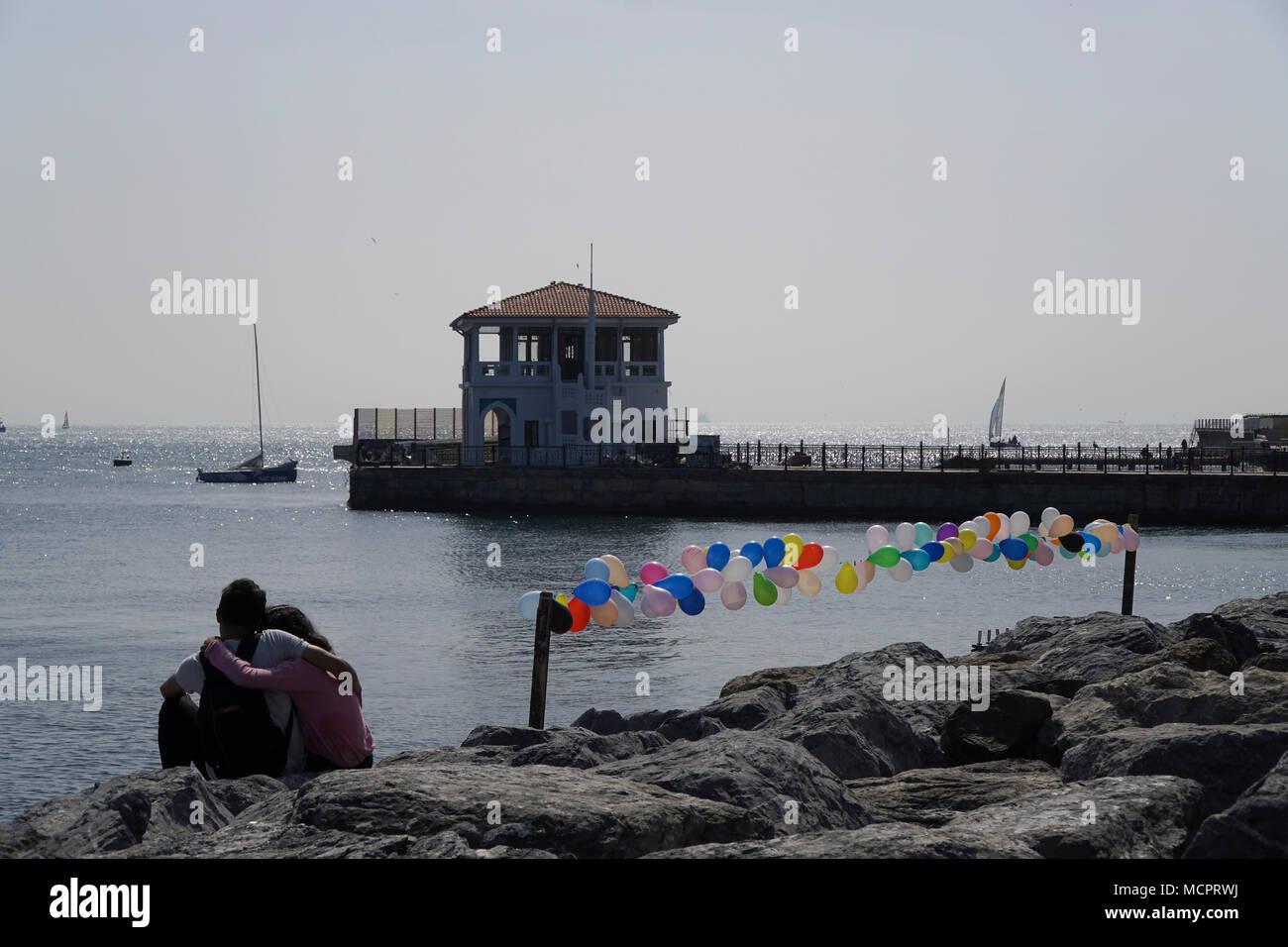 Estambul, Turquía - 14 de abril de 2018 : Una joven pareja turco están sentados en las rocas y abrazando a la playa de Kadikoy, distrito de moda. Imagen De Stock