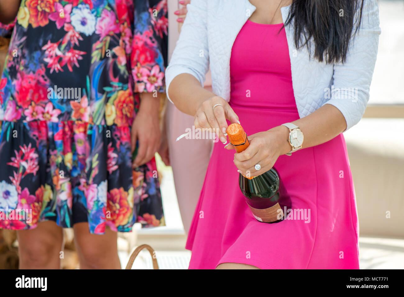 Chica en vestido rosado es la apertura de botella de champán para ...