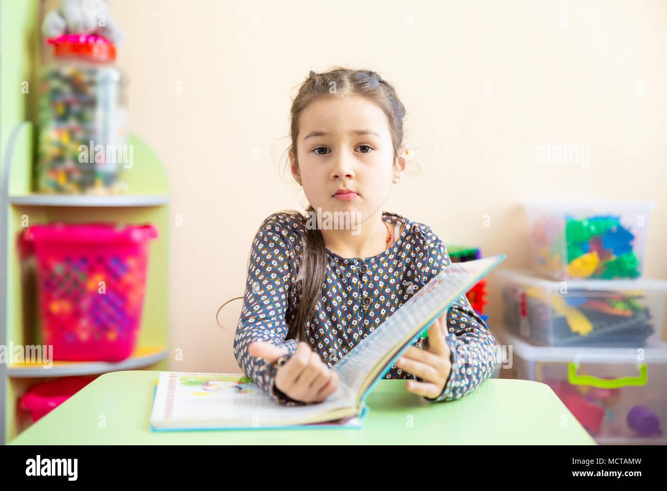 Cute Little Girl haciendo los deberes, leer un libro, escribir, páginas para colorear y pintar. Los niños de la pintura. Los niños dibujar. Niño con libros en casa. Los niños preescolares aprenden a leer y a escribir. Niño creativo Imagen De Stock