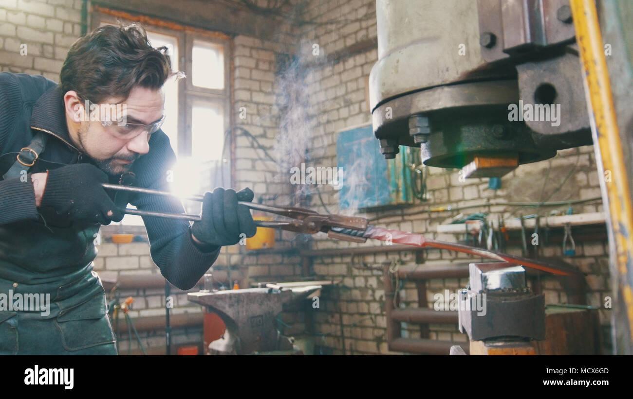 Hombre herrero en el taller de forja de hierro caliente rojo sobre el yunque - small business Imagen De Stock