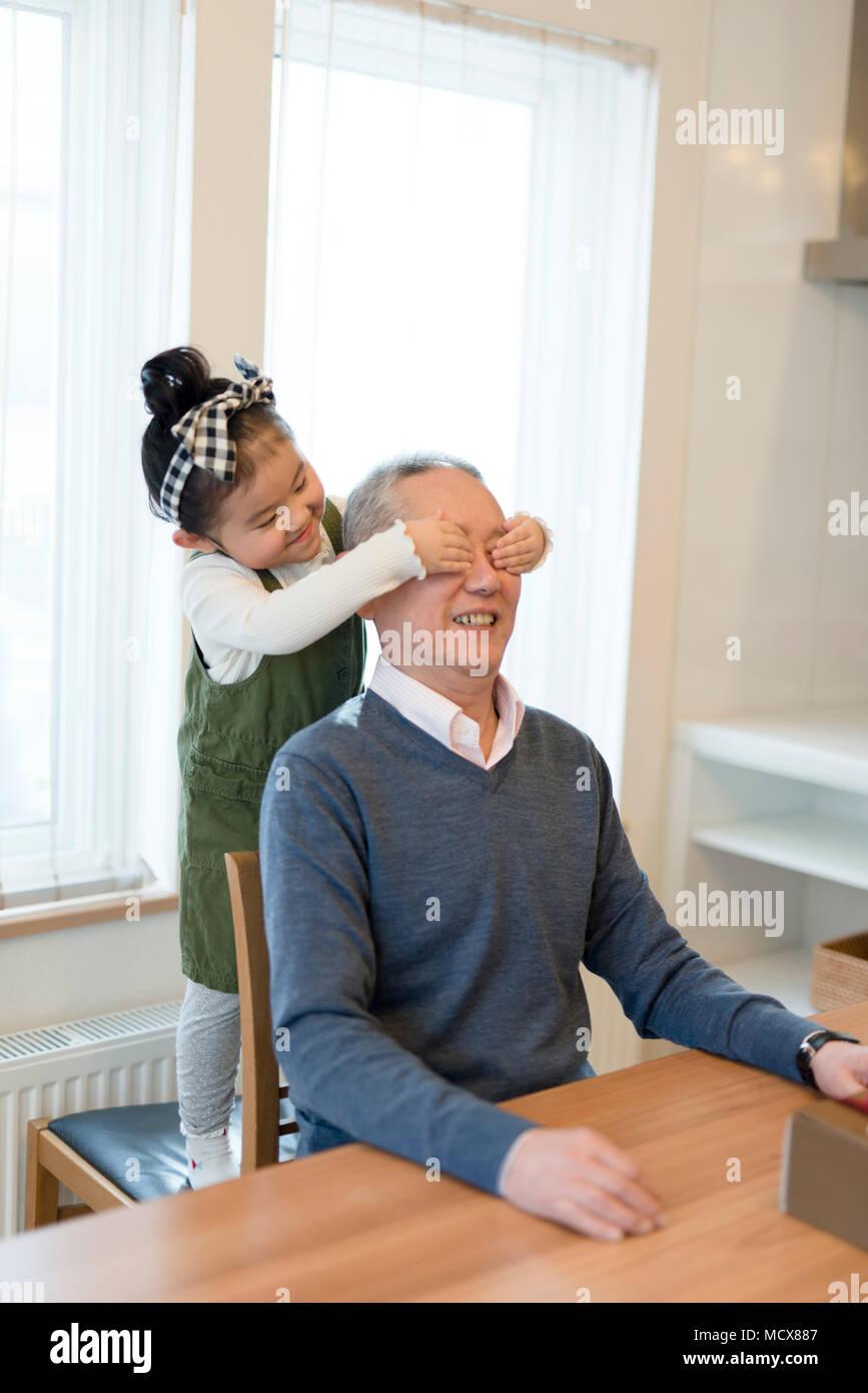 Nieto que cubre los ojos del abuelo Imagen De Stock
