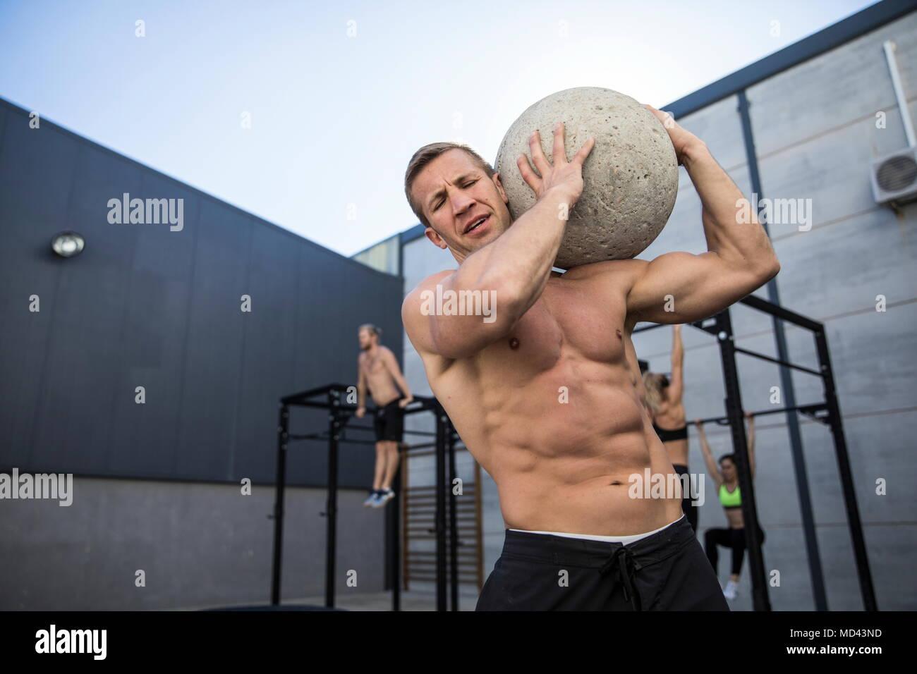 Cuatro personas haciendo ejercicio en el gimnasio, el hombre en primer plano utilizando piedra atlas Imagen De Stock