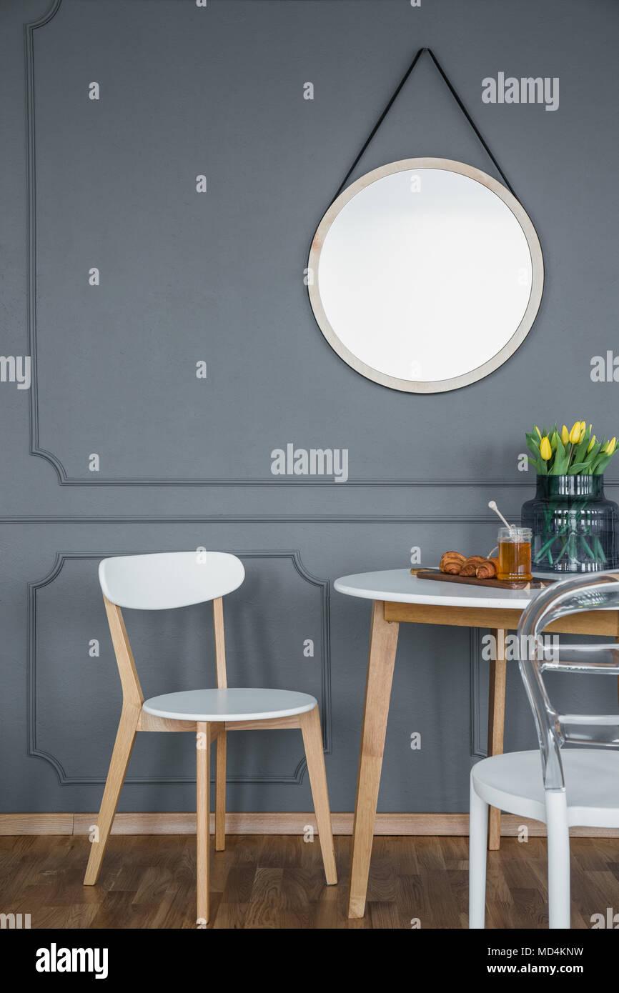 Espejo redondo con marco en una pared gris con molduras de madera ...