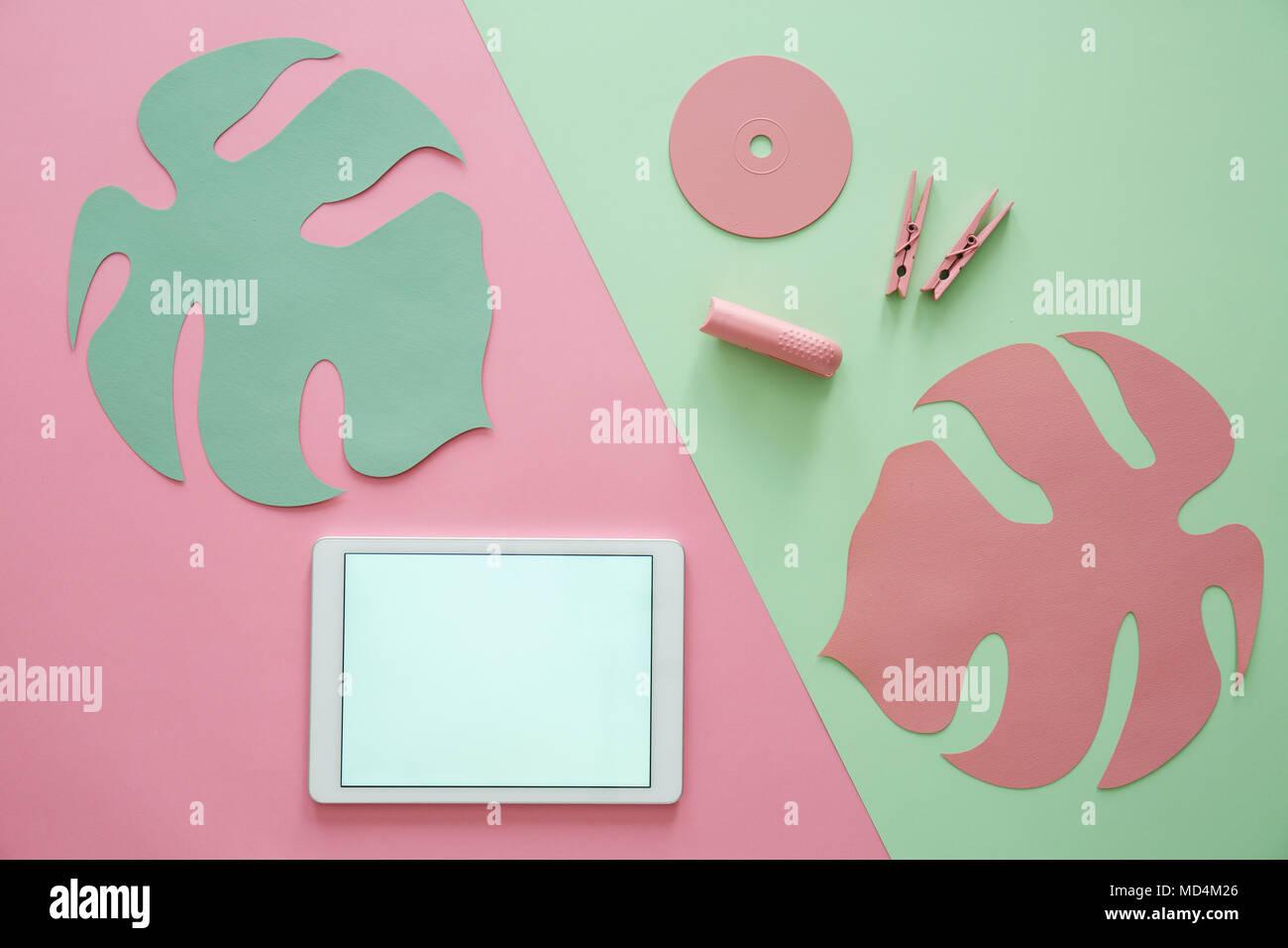 Hoja rosa sobre fondo verde y copie el espacio en una tableta con marco blanco Foto de stock