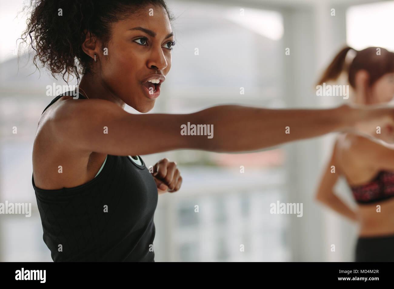 Joven africano realizando intensos trabajos de perforación en el gimnasio. Joven Mujer slim en ropa deportiva haciendo ejercicio durante el intenso entrenamiento de circuito. Imagen De Stock