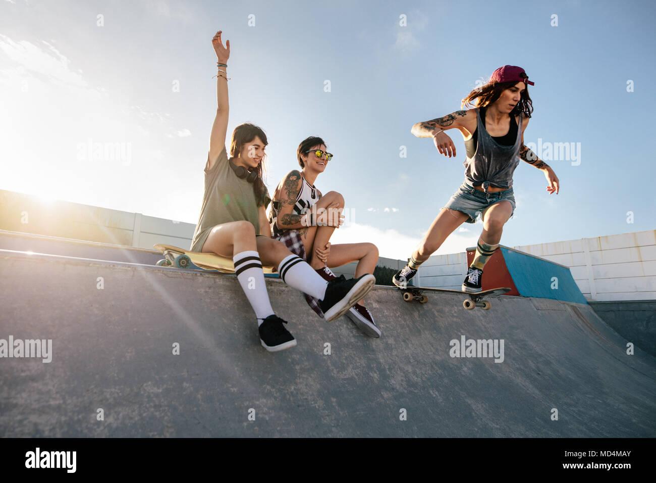 Dos jóvenes mujeres sentadas en patinaje rampa con una chica que practica  el skateboarding. Skateboarding 582b28d9972