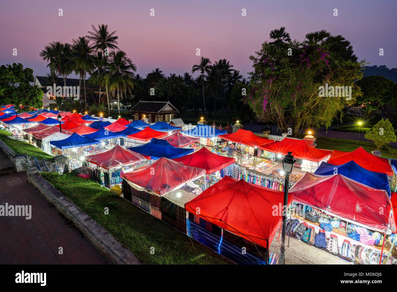 Muchos iluminados puestos de mercado en el mercado de la noche en Luang Prabang, Laos, vistos desde arriba al anochecer. Imagen De Stock