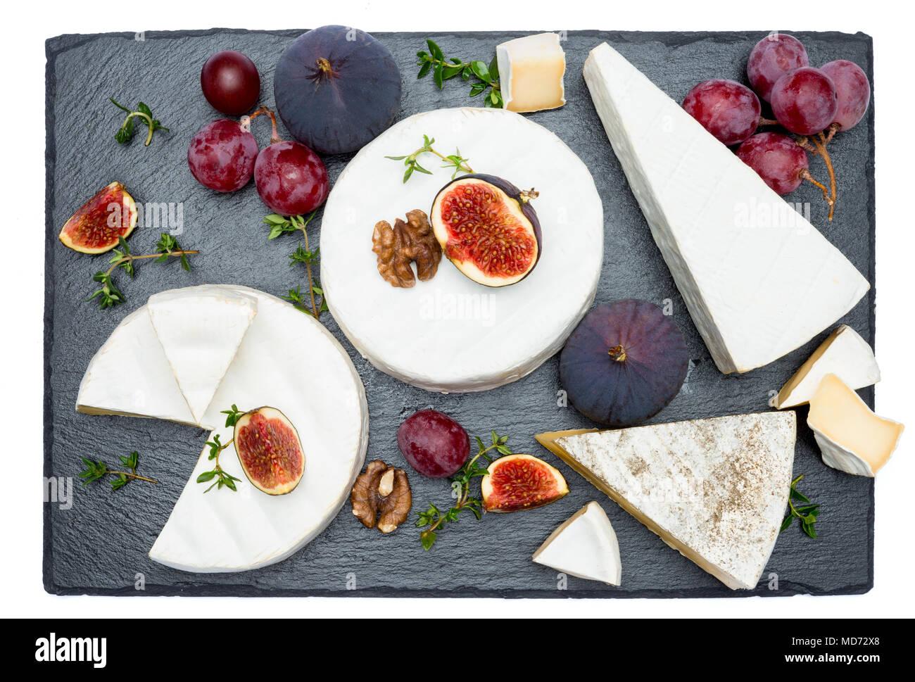 Del queso Camembert y corte un trozo de piedra sirviendo a bordo Foto de stock