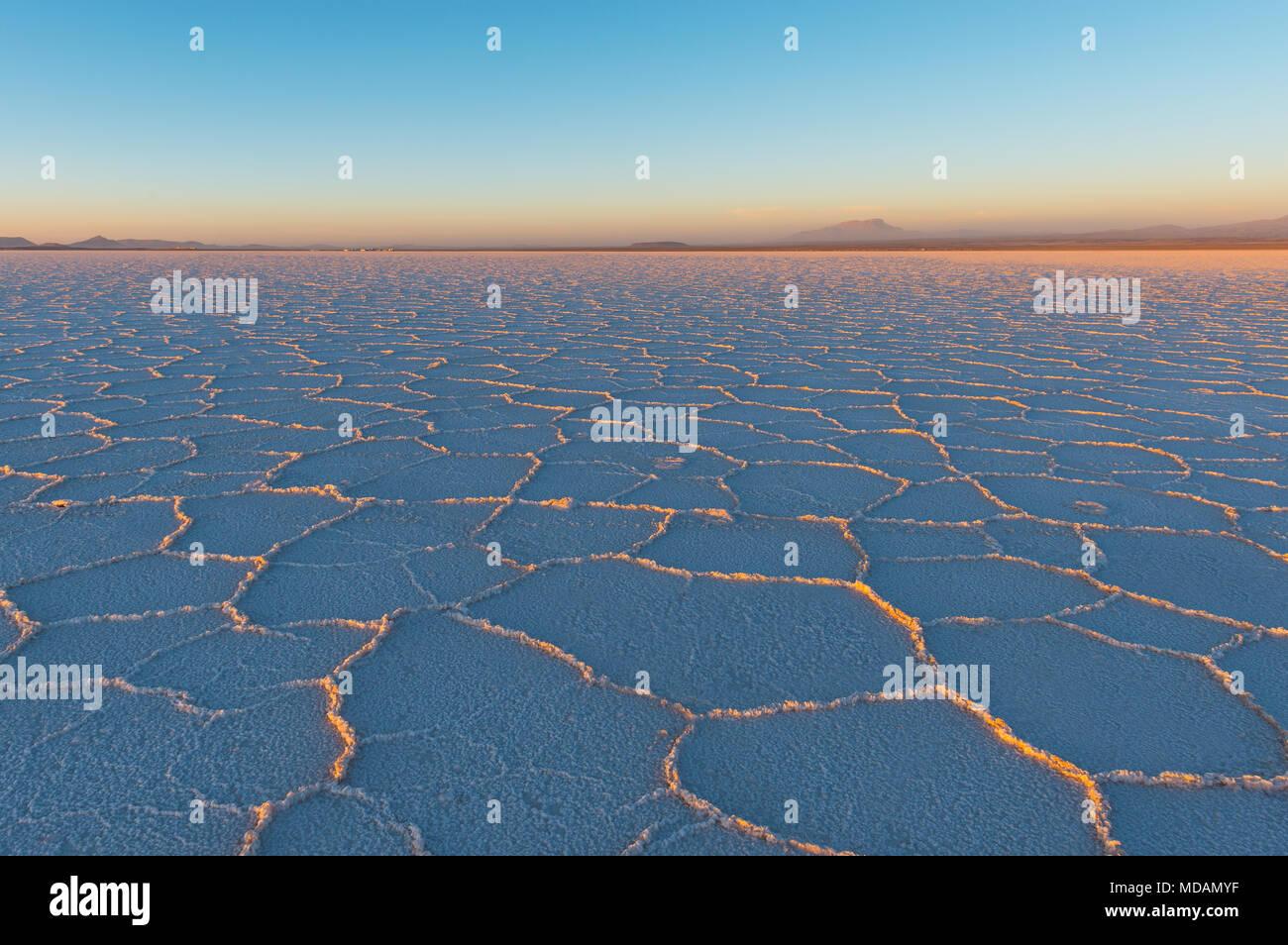 Puesta de sol en el Salar de Uyuni (Salar de Uyuni) con los últimos rayos del sol brillando en el hexágono formaciones minerales, Bolivia, América del Sur. Imagen De Stock