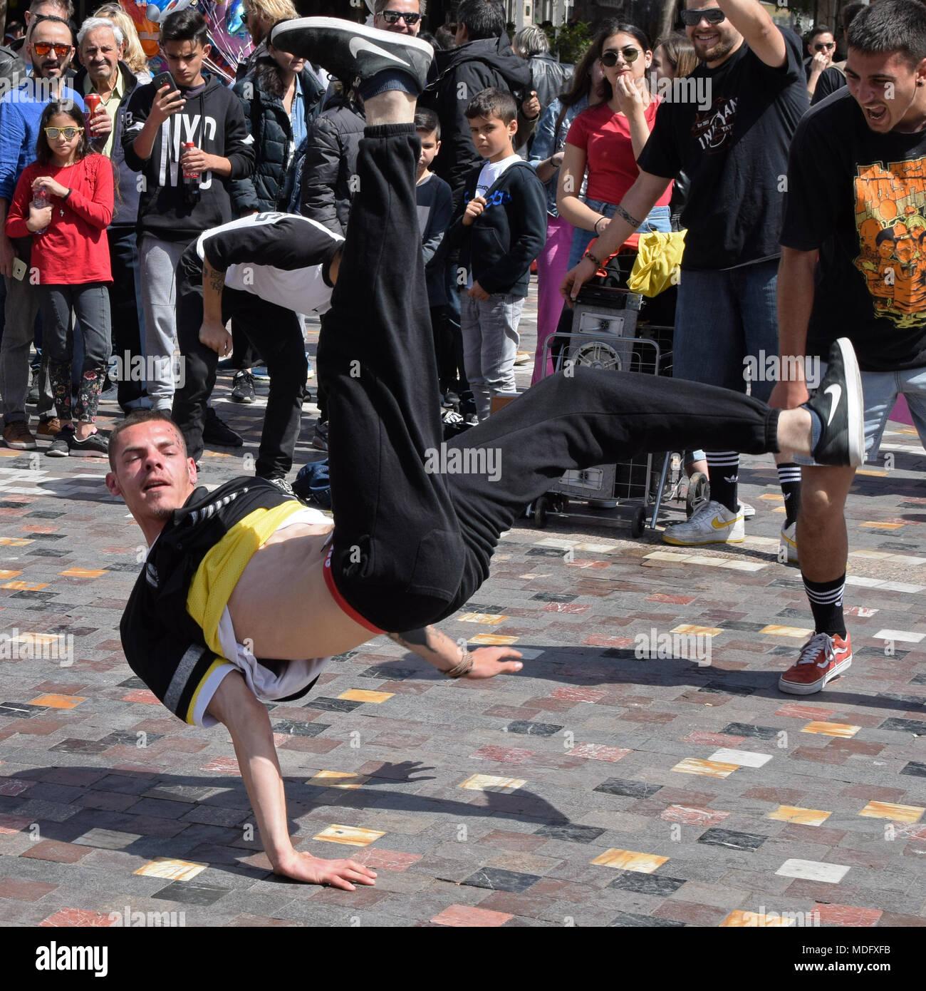 Atenas, Grecia - Abril 1, 2018: Breakdancer actuando en una plaza pública y multitud de personas. El baile de la calle la cultura juvenil. Imagen De Stock