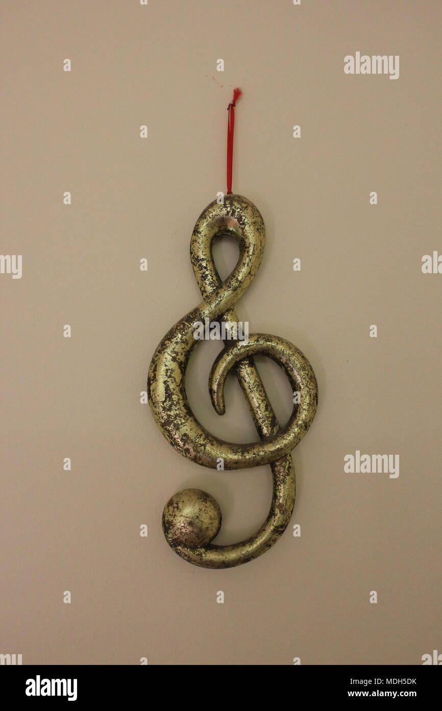 Costo de música metálica decorativa símbolo colgado en una pared, en un estudio de música. Imagen De Stock