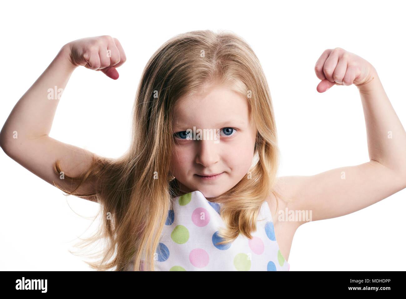 Una chica joven con el pelo rubio muestra sus músculos sobre un fondo blanco. Imagen De Stock