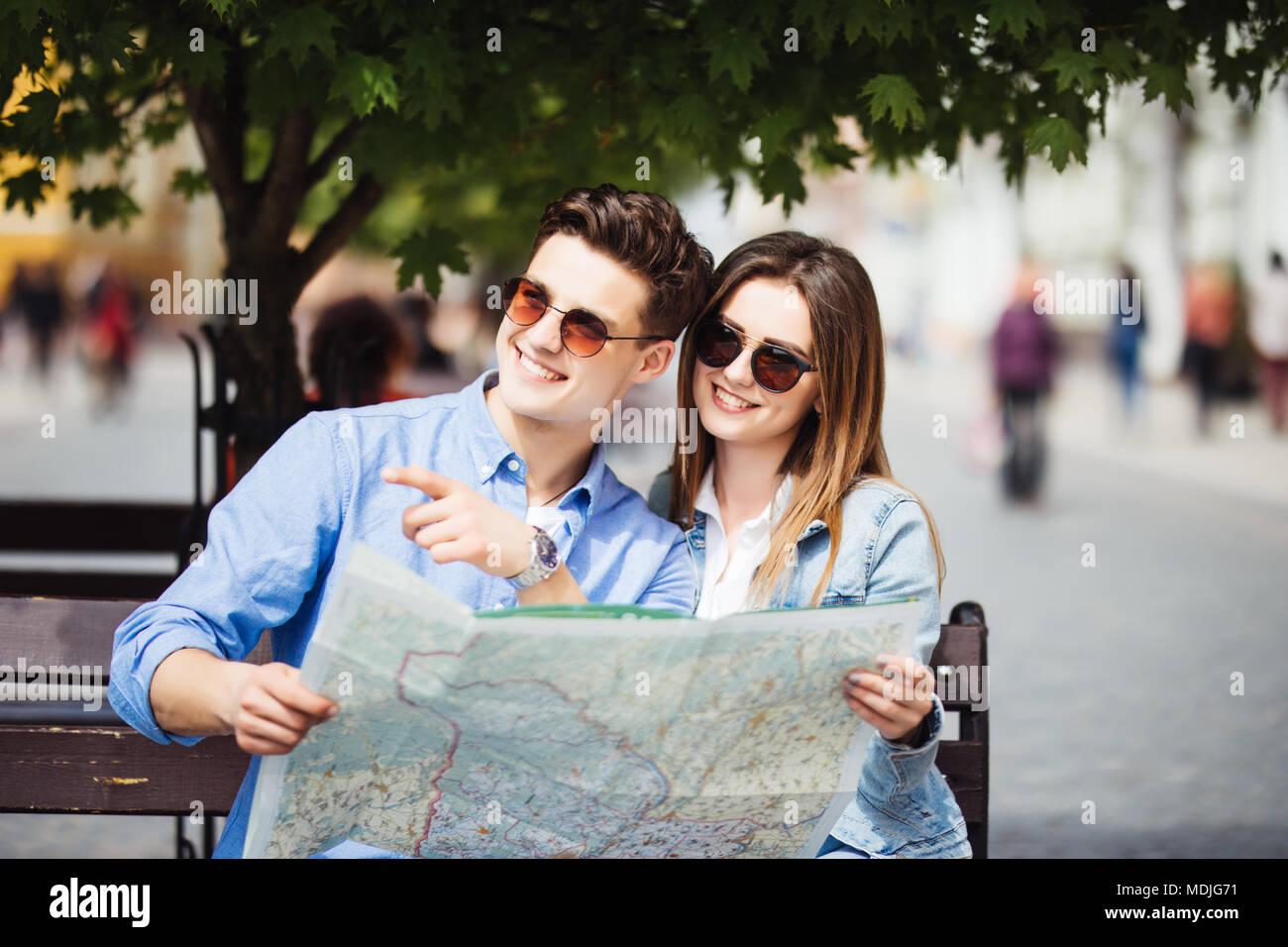 Par de turistas buscando ubicación sentado en un banco durante un viaje de verano Imagen De Stock