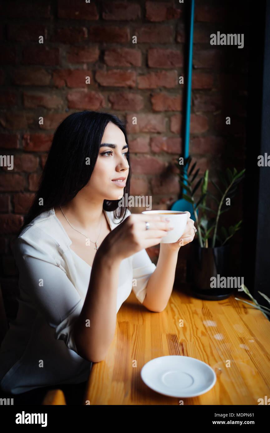 Mujer joven tomaba un café en una cafetería al aire libre. Imagen De Stock