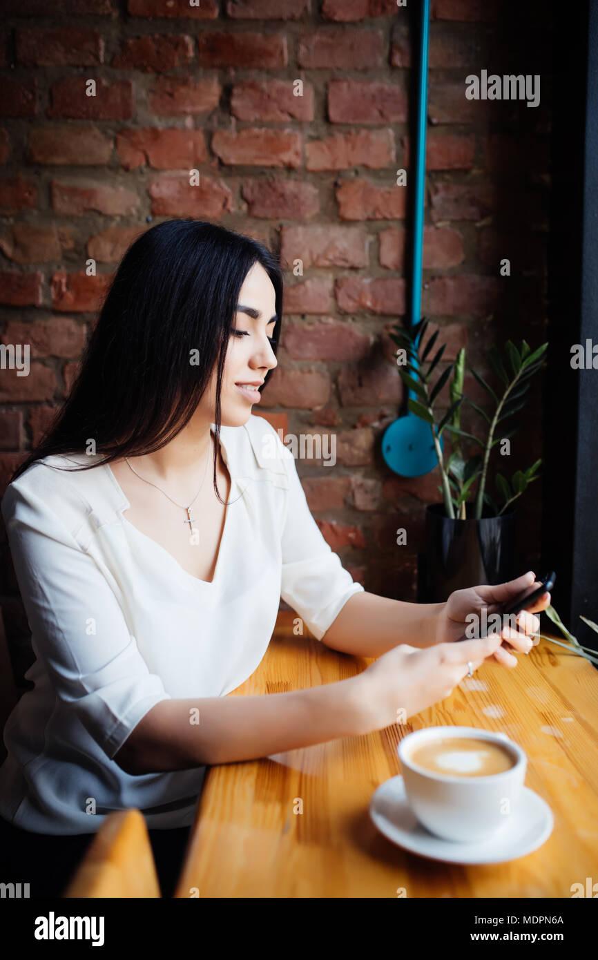 Retrato de joven empresaria utilice el teléfono móvil mientras se está sentado en la cafetería cómoda durante el descanso de trabajo Imagen De Stock