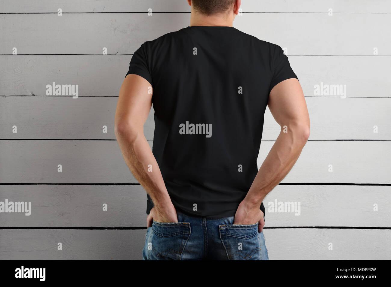 e1d342a2b Plantilla de una camiseta negra sobre un hombre fuerte con las manos en el  bolsillo trasero de los pantalones vaqueros sobre un fondo de madera. Vista  desde ...
