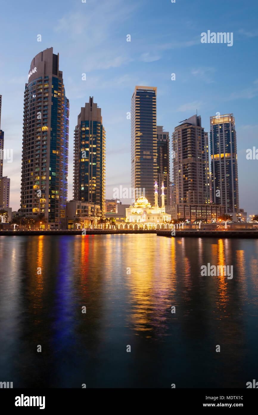 Mezquita iluminadas por debajo de la arquitectura moderna y torres se refleja en el agua en el Dubai Marina, Dubai, Emiratos Árabes Unidos, Oriente Medio Imagen De Stock