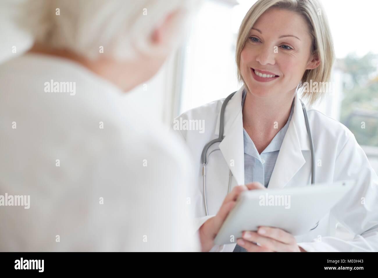 Doctora utilizando digital tablet con paciente. Foto de stock