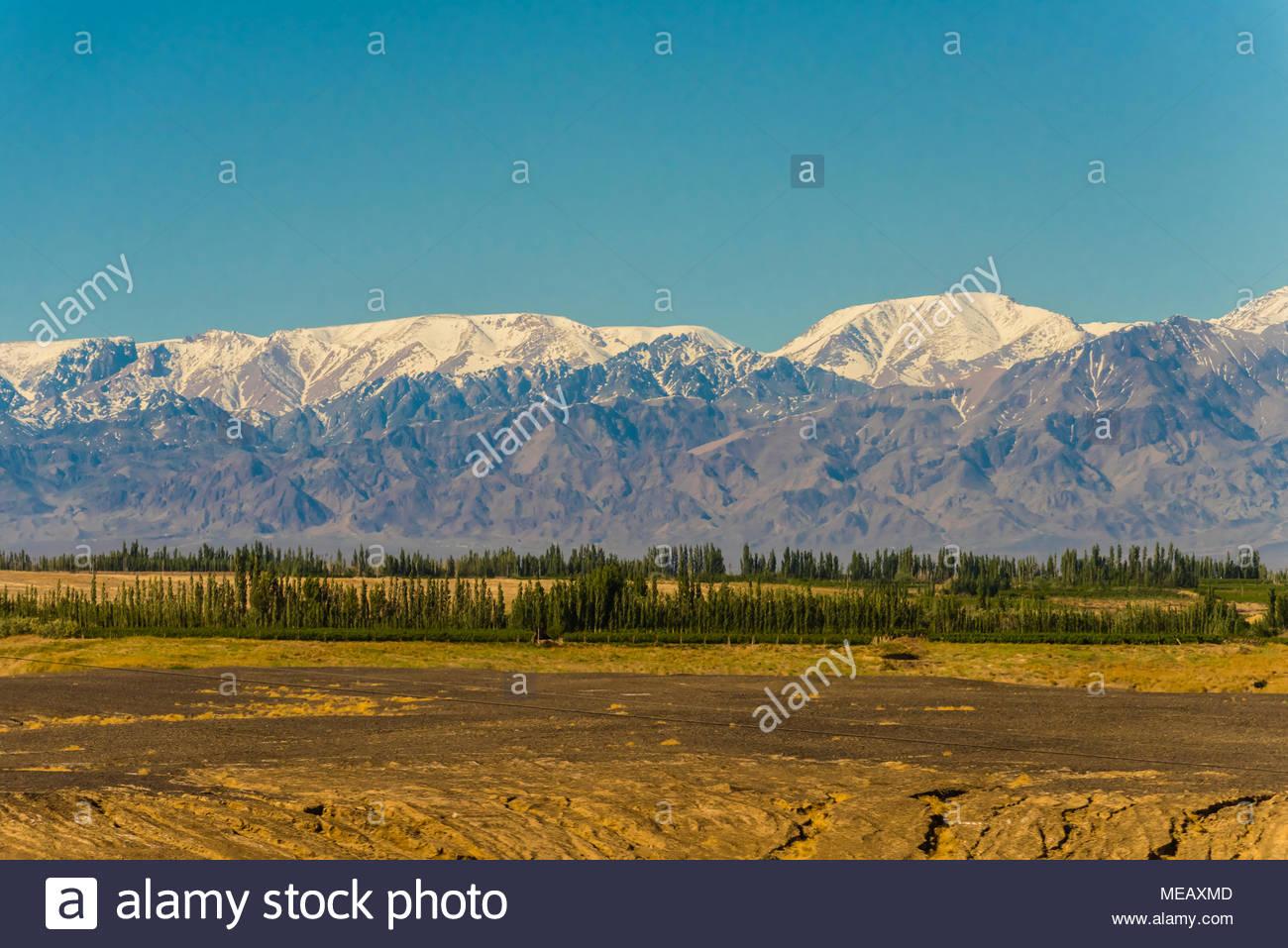 Las montañas cubiertas de nieve, visto desde el tren entre en la provincia de Gansu y Dunhuang Turpan en la provincia de Xinjiang. Al norte (detrás de las montañas) se encuentra la Imagen De Stock