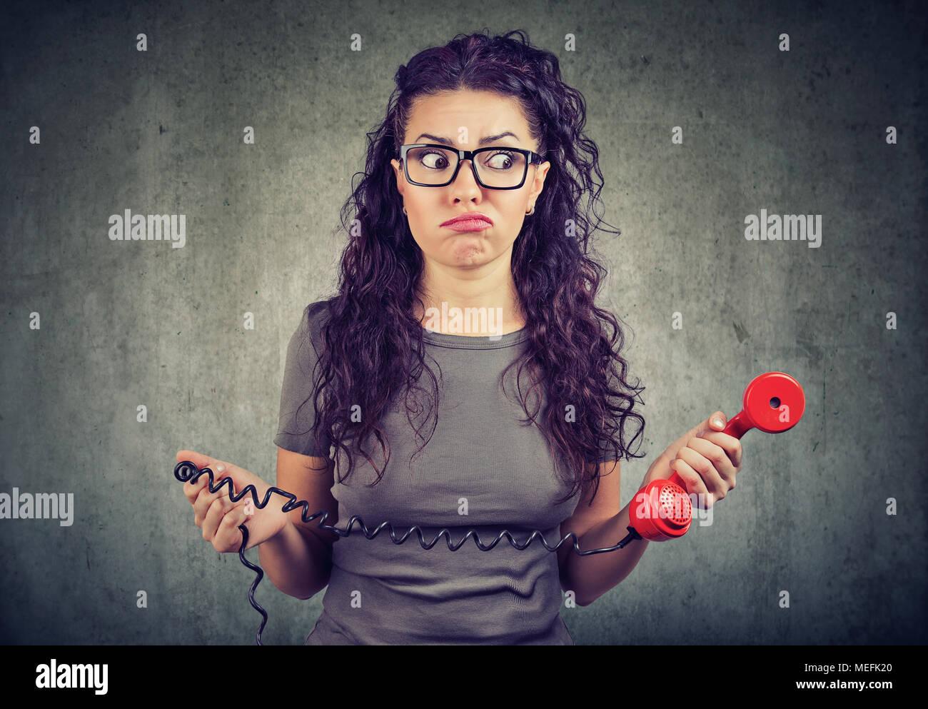 Mujer joven mirando con desconcierto la celebración antiguo teléfono rojo. Imagen De Stock