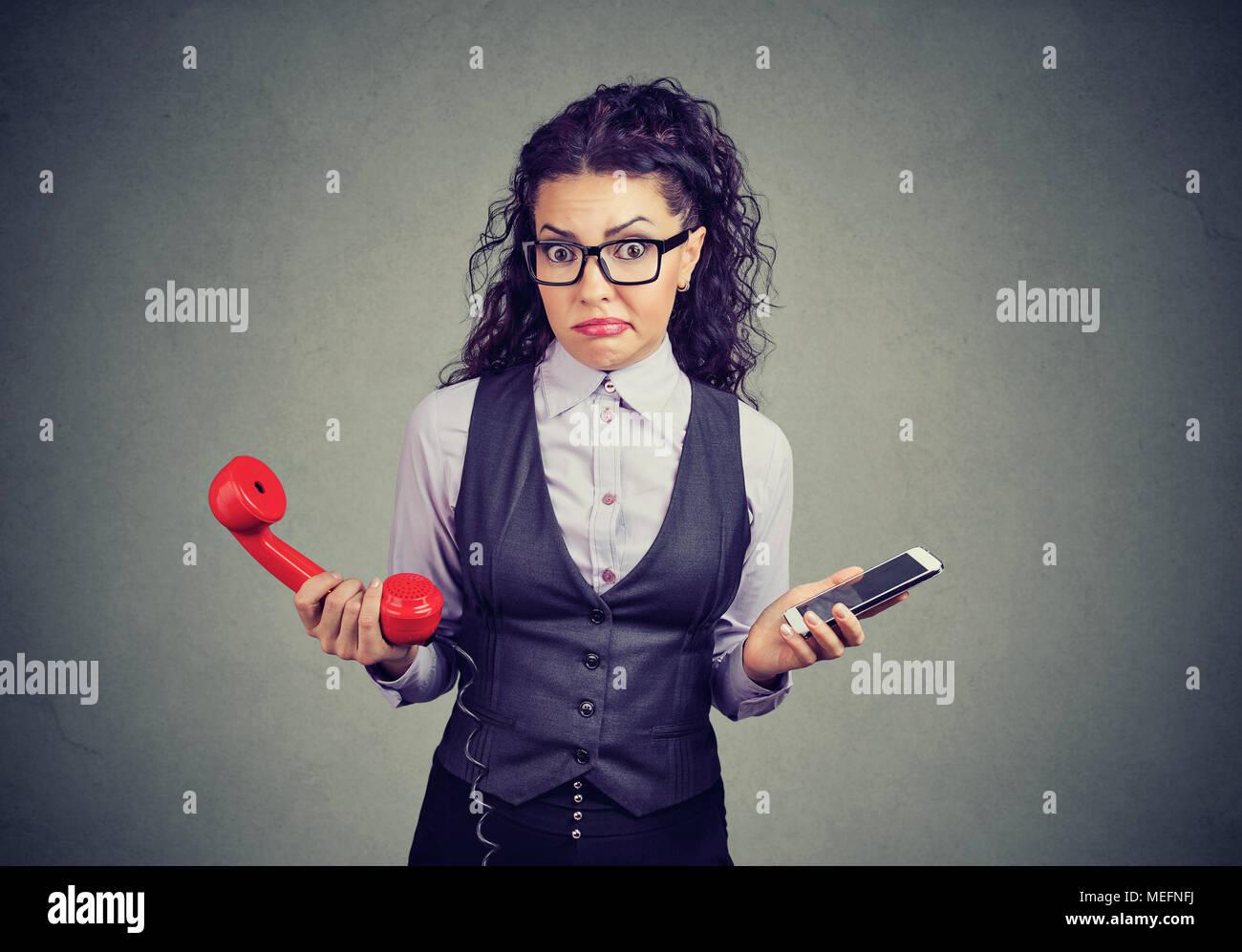 Mujer formal en vidrios celebración de teléfono antiguo y nuevo smartphone mirando perplejos ante la cámara. Imagen De Stock