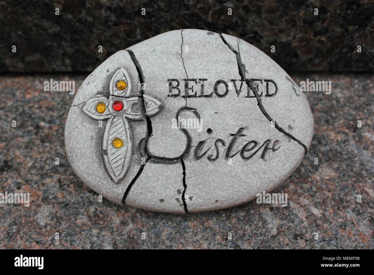 """Memorial de roca que dice """"Querida Hermana"""" junto a un decorado cruz. Imagen De Stock"""