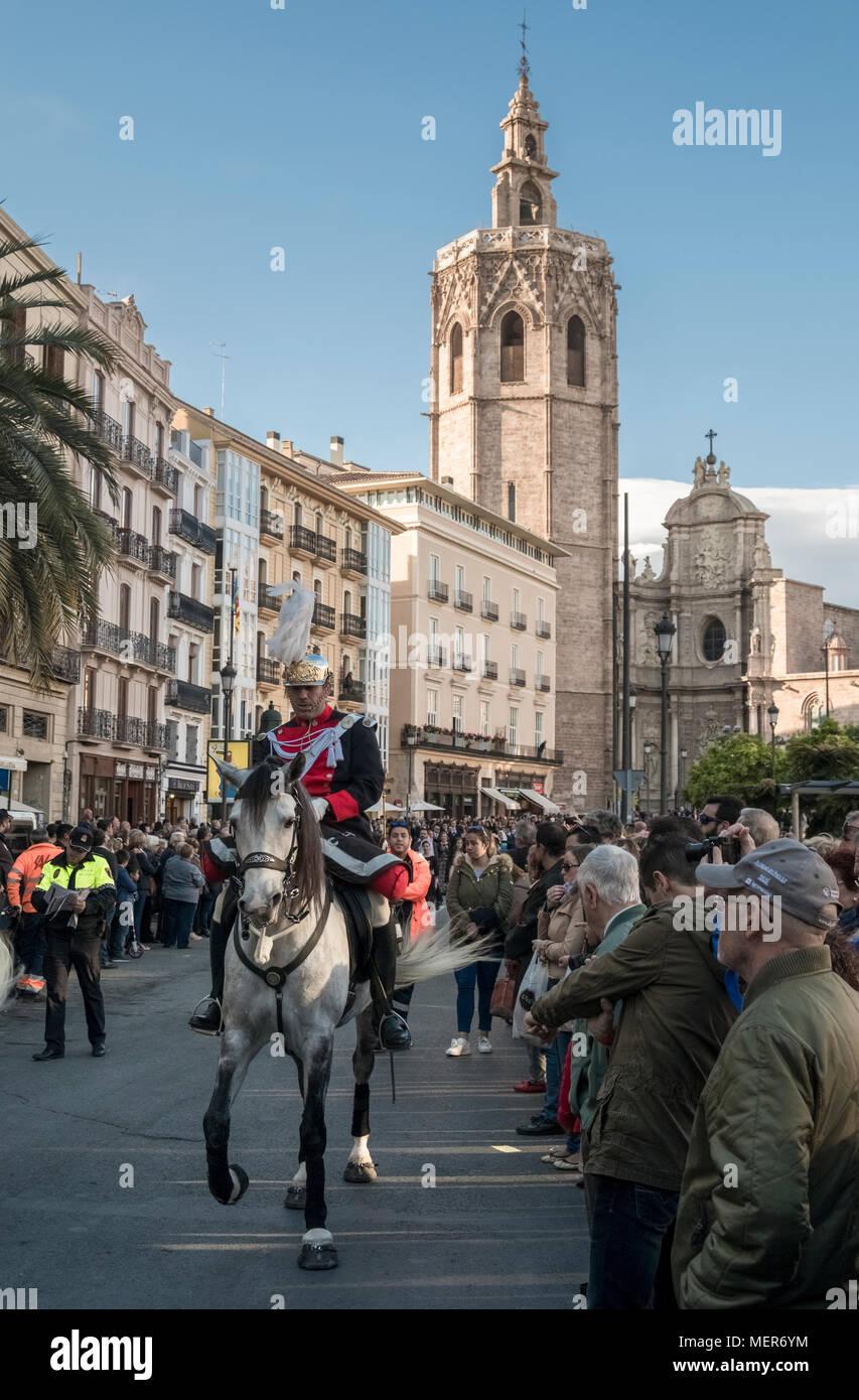 El 9 de abril de 2018, un jinete lleva una procesión religiosa desde St Marys Catedral por multitudes a lo largo de las calles de Valencia, España. Imagen De Stock