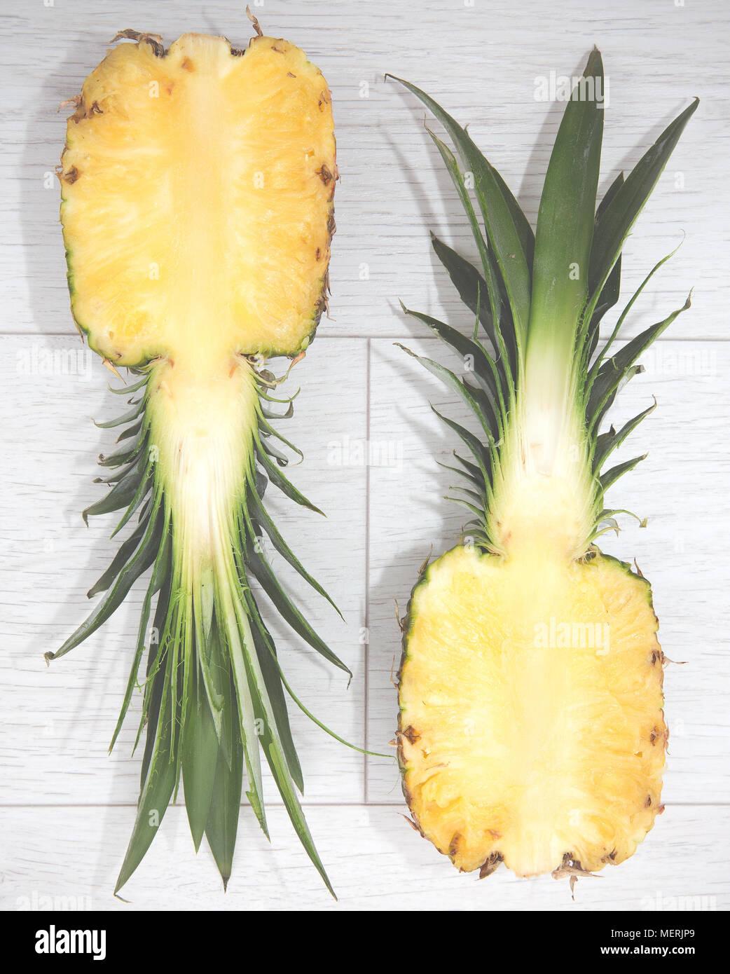 Mirando de arriba abajo en una piña que ha sido cortada en dos mitades, revelando el interior de la pulpa del fruto en una sección transversal Foto de stock