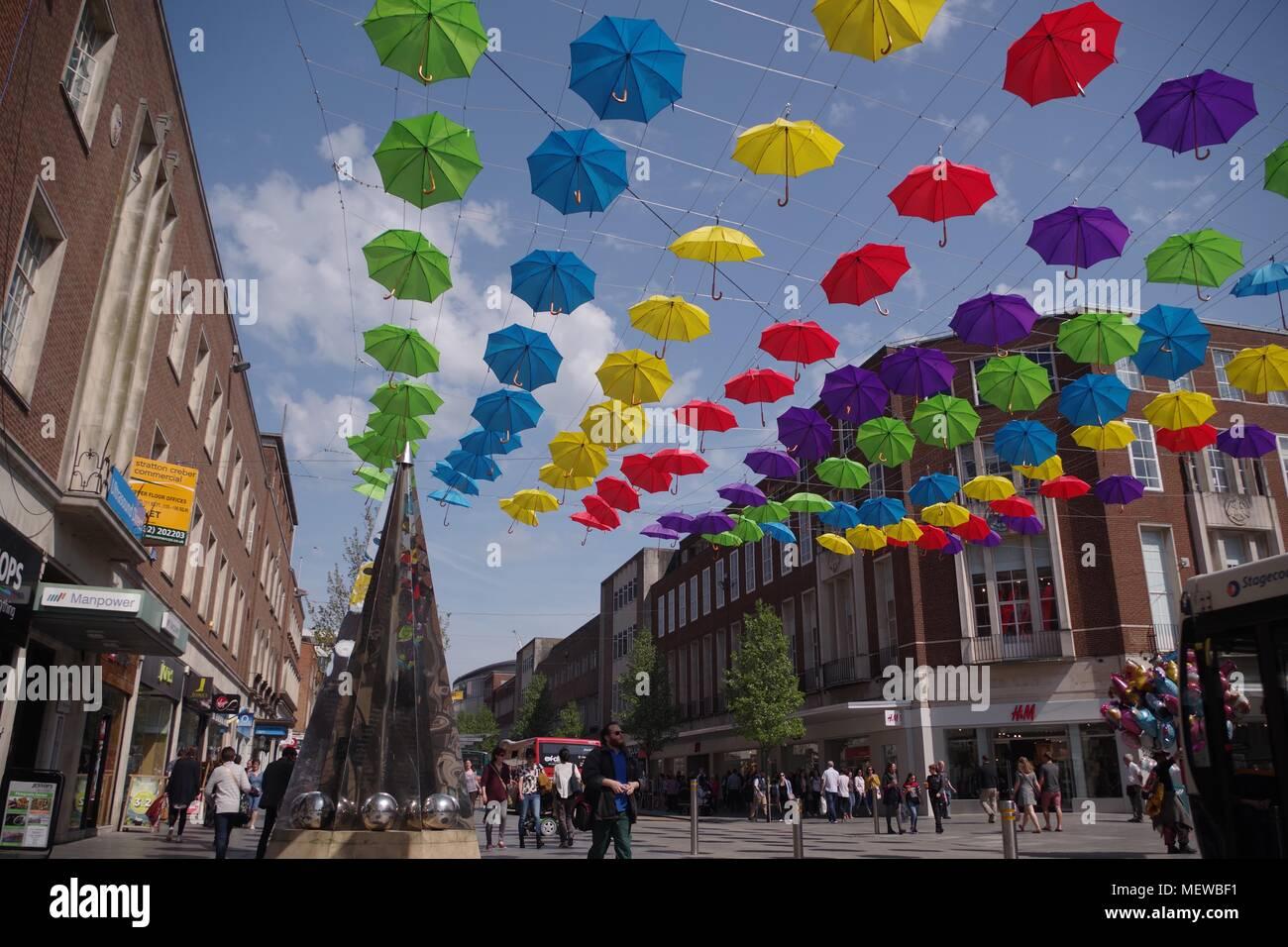 La Exeter Enigma y coloridas sombrillas de primavera. Exeter High Street, Devon, Reino Unido. Abril, 2018. Foto de stock
