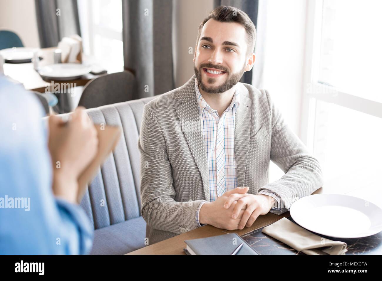 Empresario alegre pone orden en restaurante. Imagen De Stock