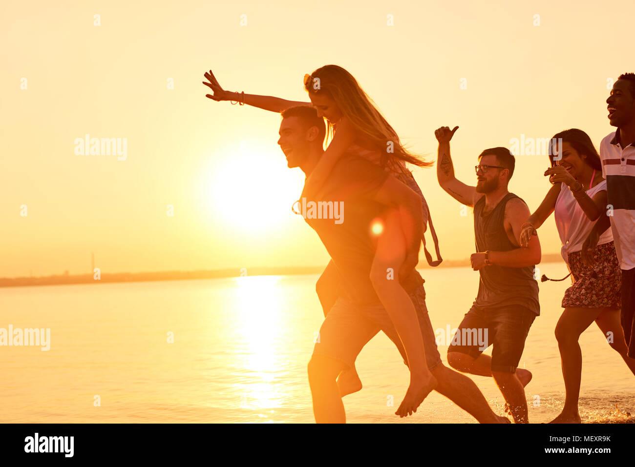 Hilarantes amigos corriendo sobre el agua en la luz del atardecer Imagen De Stock