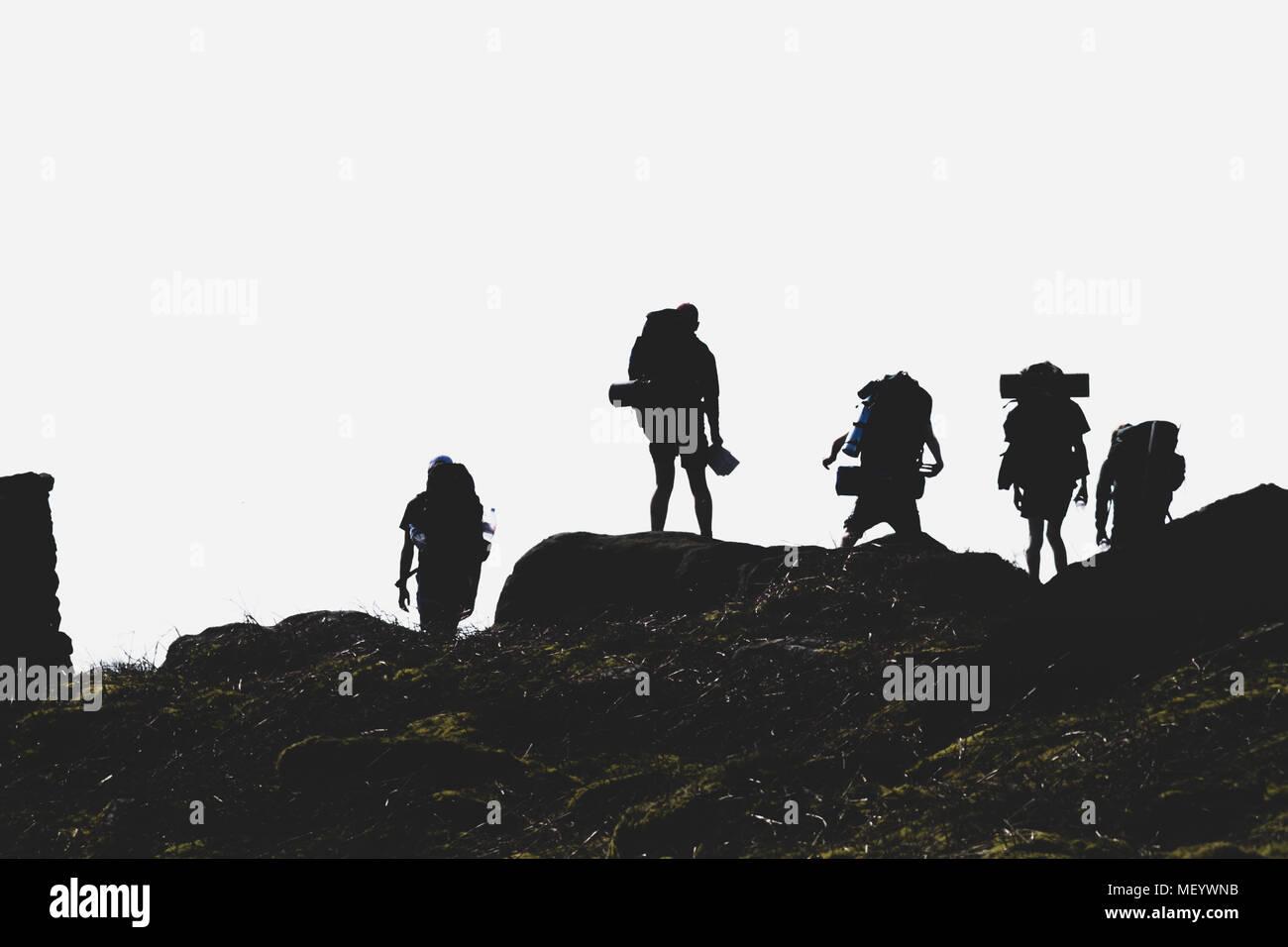 Adolescentes un Duque de Edimburgo expedición con pesadas mochilas para acampar siluetas contra el sol Imagen De Stock
