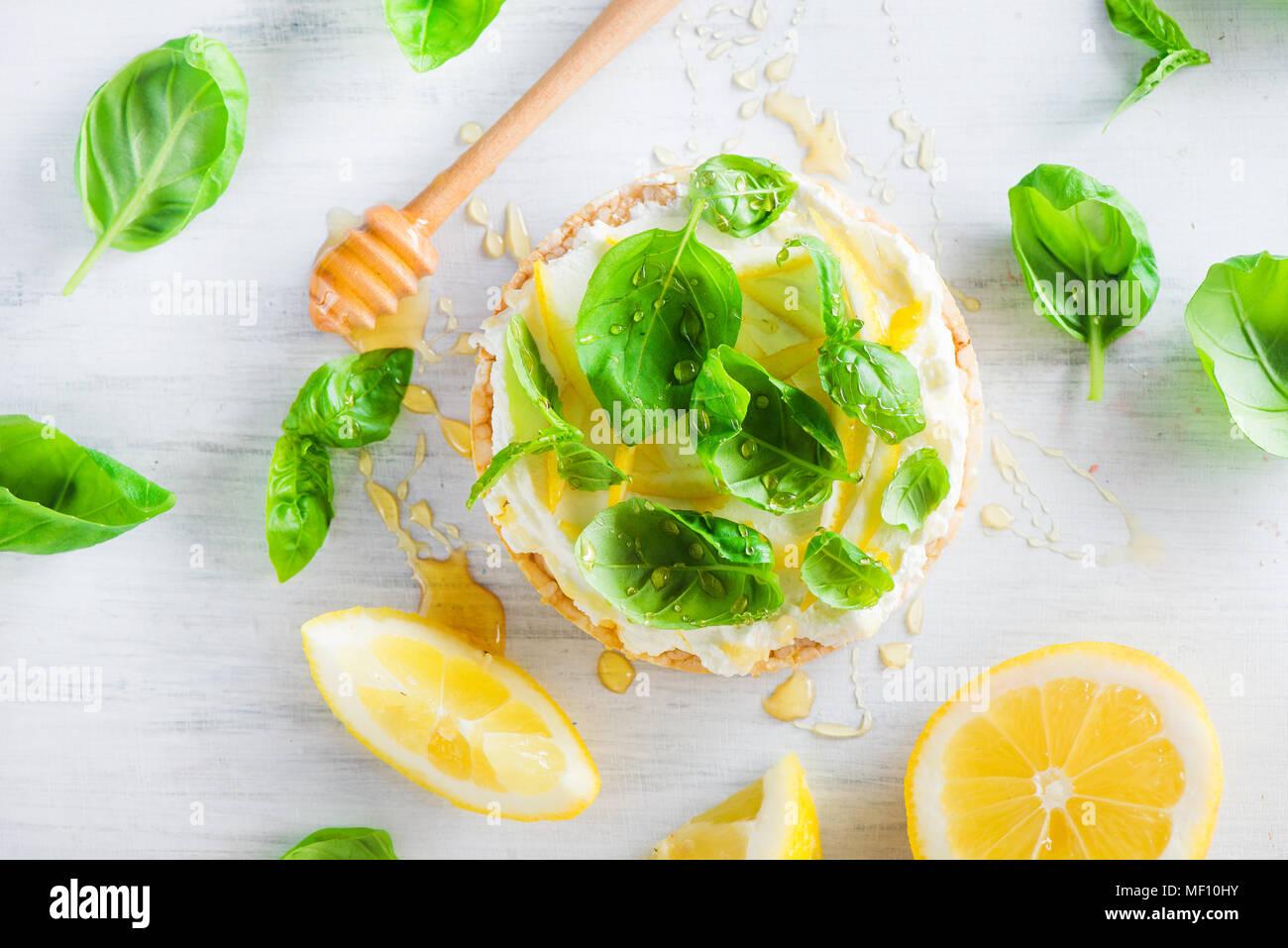 Refrigerio saludable con pan crujiente, la ralladura de limón, la miel y la albahaca. Sencilla receta de aperitivo. Imagen De Stock