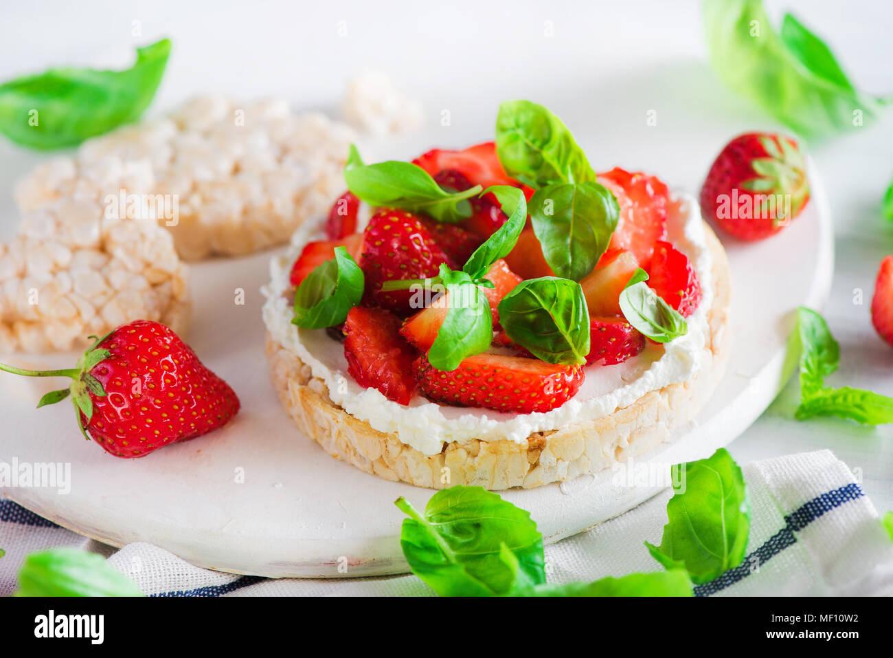 Refrigerio saludable con pan crujiente, fresas frescas, queso de cabra y hojas de albahaca. Sencilla receta de aperitivo. Imagen De Stock