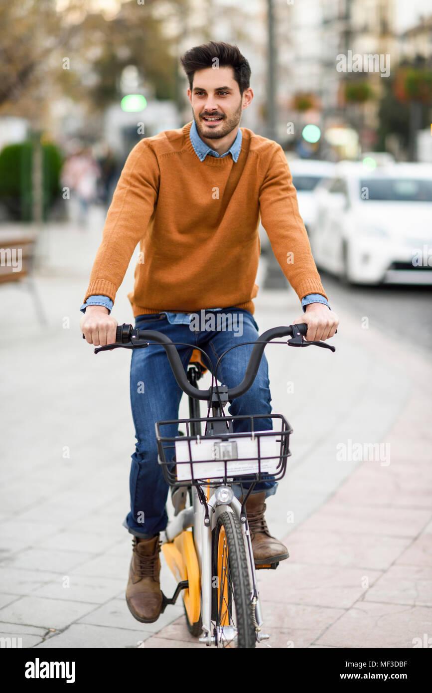 España, Andalucía, Granada. Apuesto joven en bicicleta compartida en la ciudad. Concepto de estilo de vida. Imagen De Stock