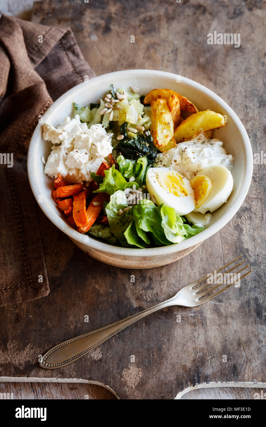 Almuerzo en la cubeta con papas cocidas y la zanahoria, herbed requesón, ensalada, Mangold, feta y huevo cocido Imagen De Stock