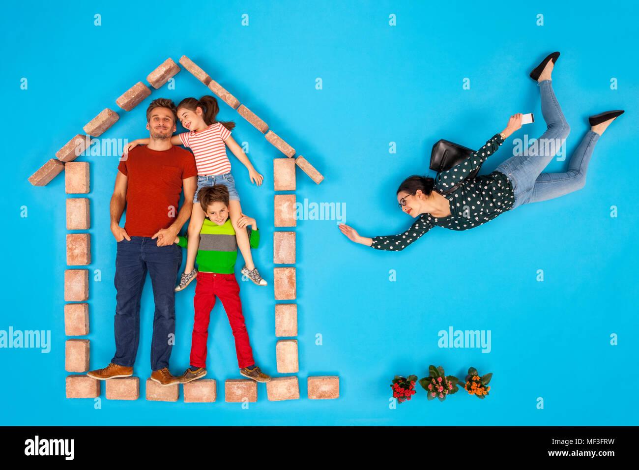 Padre e hijos esperando en casa, mientras la madre llega a casa del trabajo Imagen De Stock