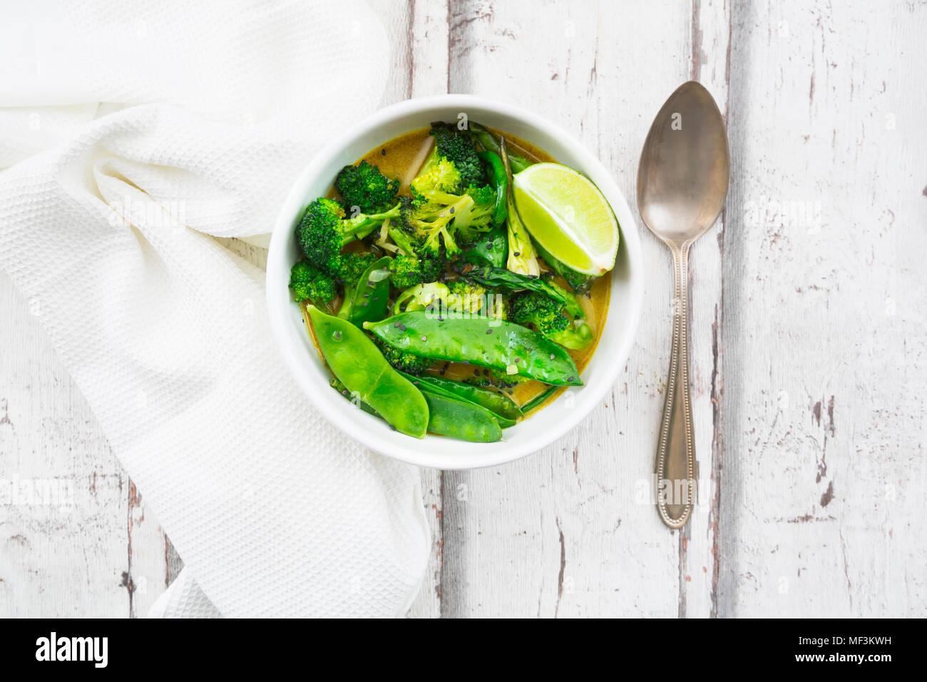 Green curry tailandés con brócoli, pak choi, guisantes, espinacas baby, limón y arroz Imagen De Stock