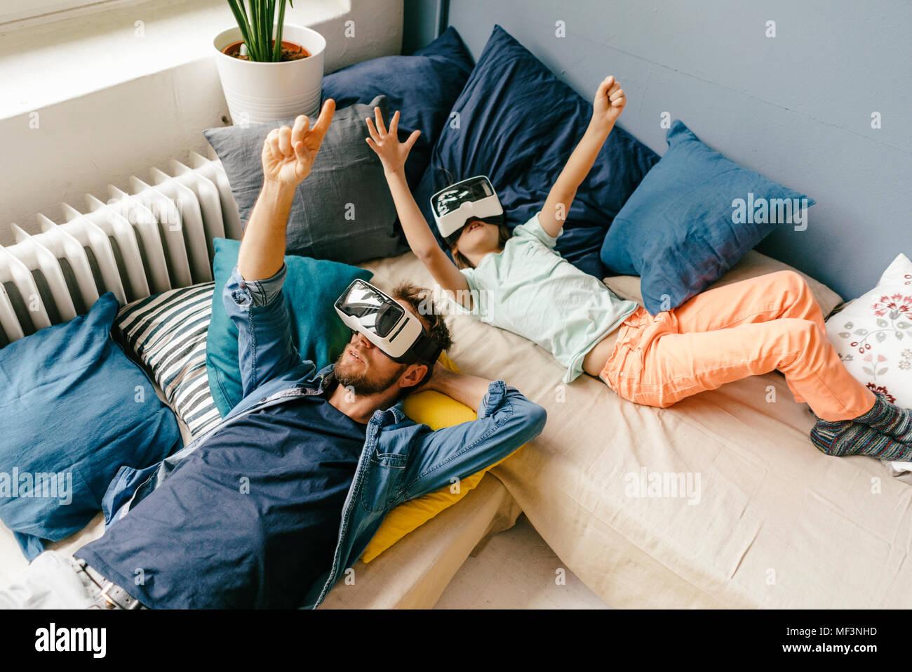 Padre e hijo llevaba gafas VR acostado en casa Foto de stock