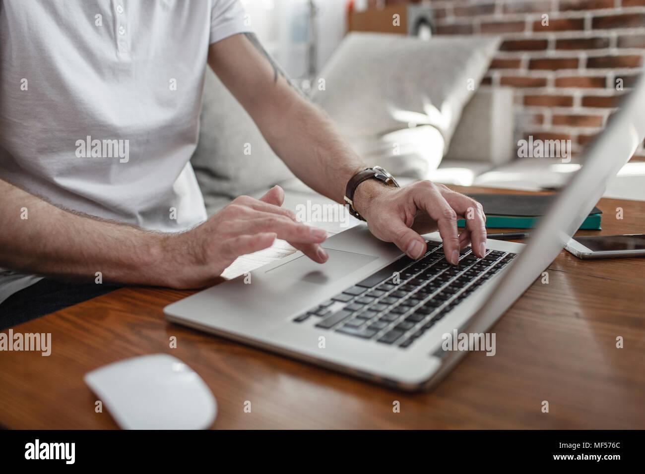 Las manos del hombre en el teclado y el touchpad del portátil, vista parcial Imagen De Stock