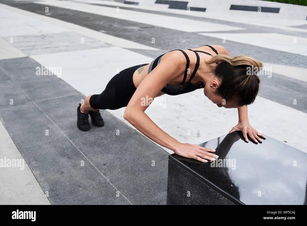 Colocar mujer haciendo flexiones en el exterior Imagen De Stock