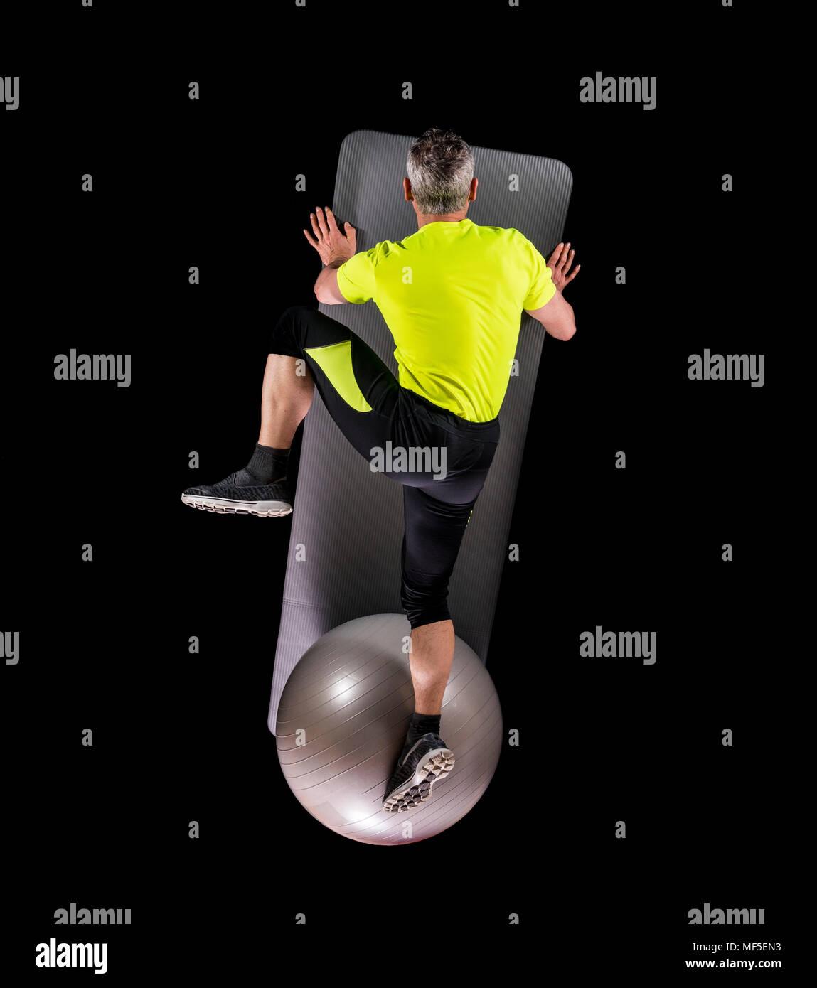 El hombre ejerciendo con bola de gimnasia, vista superior Imagen De Stock