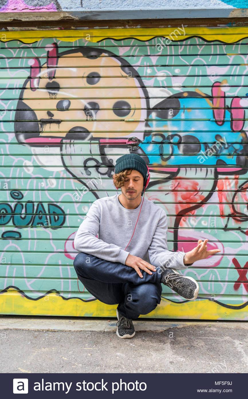 Joven escuchando música con auriculares haciendo ejercicio de yoga delante de graffiti Foto de stock