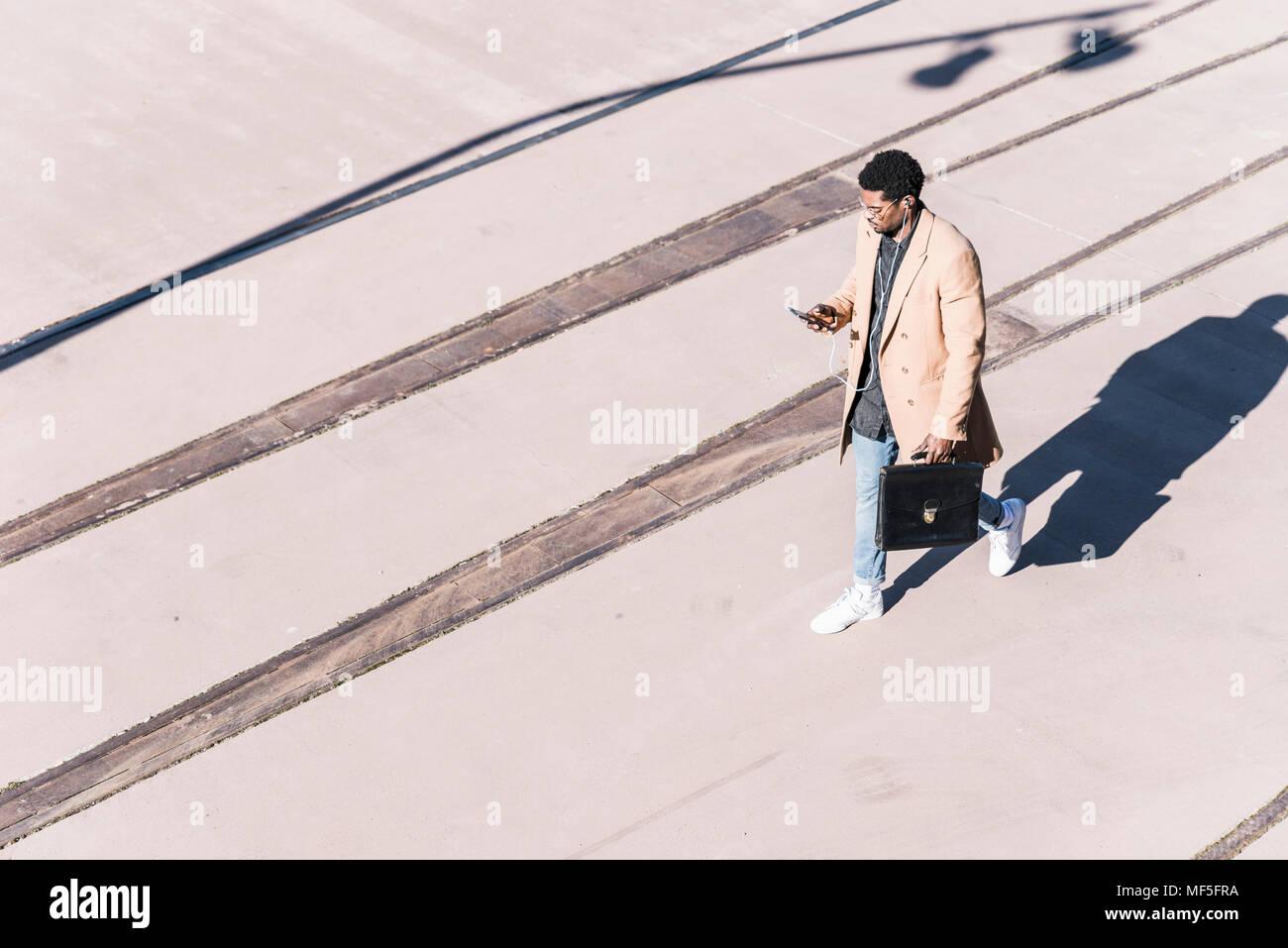 Empresario caminando afuera con maletín, teléfono celular y auriculares Imagen De Stock
